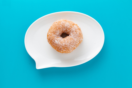 Foto per A doughnut coated with sugar on plate shaped like text bubble, on blue background. - Immagine Royalty Free