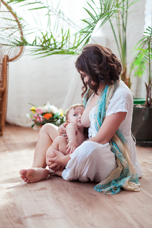 Photo for Beautiful young mother breastfeeding her baby at home sitting on the floor near window and flowers - Royalty Free Image