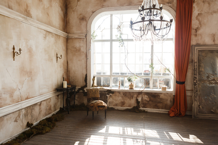 Photo for Entourage interior: wall, table and candles, crystal light, big window in an old scary abandoned house. Halloween concept - Royalty Free Image