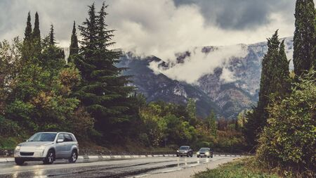 Photo pour Highway in the mountains. Cumulus clouds and mountain landscape in rainy weather. Crimea in autumn. View from the car window. Selective focus. - image libre de droit