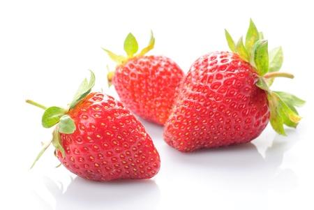 Foto de Group of fresh strawberries whith grean leaf on white  - Imagen libre de derechos