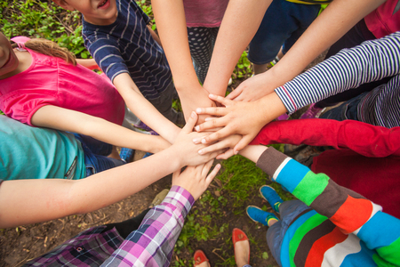 Foto de Close-up of many children's hands holding together as a team on a nature background - Imagen libre de derechos