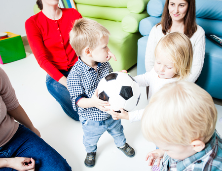 The group of little kids quarrel over a ball. Children in hysterics, because one boy intercepted the ball from others. The concept of children who are taught to share with each other