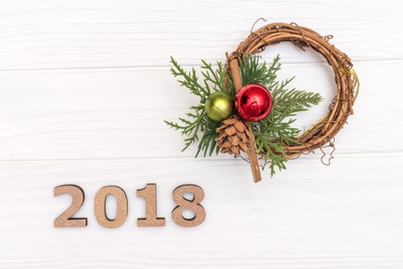 Foto de The numbers 2018 and wreath of pine branch and cone on white wooden background - Imagen libre de derechos
