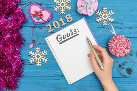 Foto de notebook with GOALS text and womans hand holding pen above with numbers 2018 and new year ornaments - Imagen libre de derechos