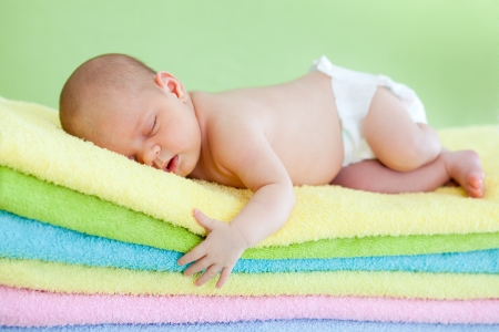 Photo pour adorable baby newborn weared cap sleeping on colourful towels - image libre de droit
