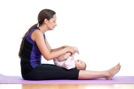 Mother doing yoga exercises with her baby