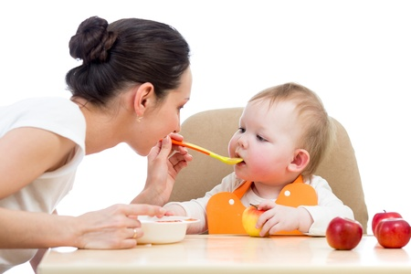 Photo pour young mother spoon feeding her baby girl - image libre de droit
