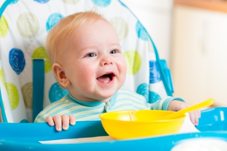 Photo pour smiling baby eating food on kitchen - image libre de droit