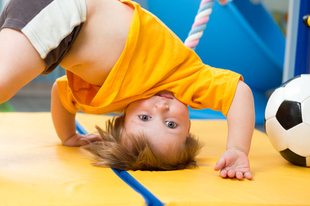 Photo pour baby standing upside down on gym mat - image libre de droit