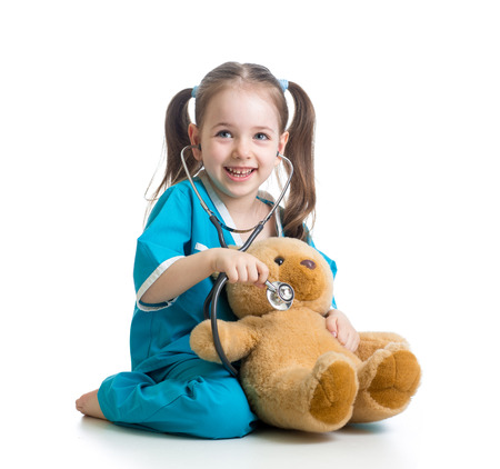Adorable child with clothes of doctor examining teddy bear toy over white