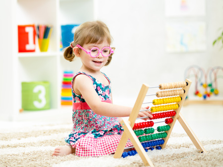 Foto de kid girl with eyeglasses playing abacus toy - Imagen libre de derechos