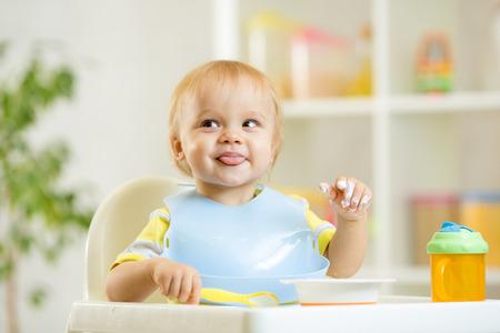 Photo pour smiling cute baby kid boy eating itself with spoon - image libre de droit