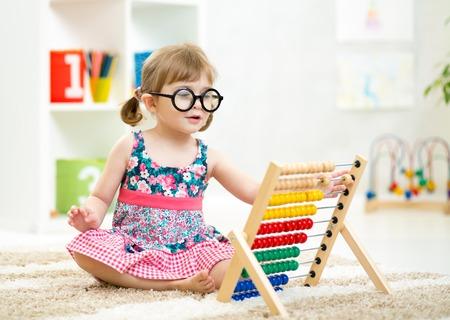 Foto de child kid weared glasses playing with abacus toy indoor - Imagen libre de derechos