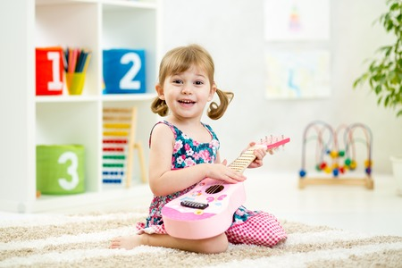 Photo for kid girl playing guitar toy at home - Royalty Free Image