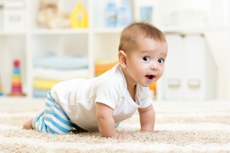 Photo pour crawling funny baby boy indoors at home - image libre de droit