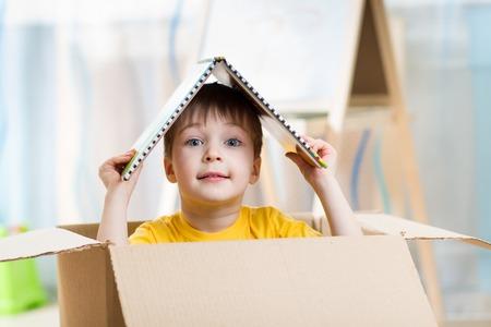Foto de kid boy playing in a toy house in children room - Imagen libre de derechos