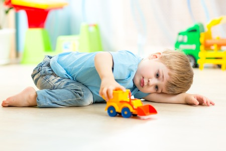 Photo pour child boy toddler playing with toy car indoors - image libre de droit