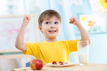 Foto per child boy eating healthy food and showing his strength indoors - Immagine Royalty Free