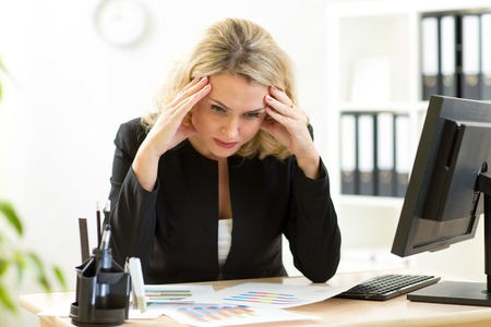 Photo for thoughtful businesswoman looking at business papers in office - Royalty Free Image