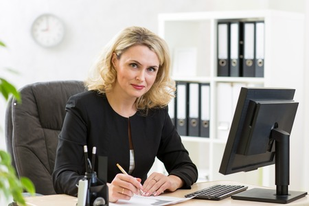 Photo pour Middle-aged pretty business woman working at pc in office - image libre de droit