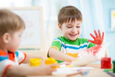 Foto de smiling kids playing and painting at home or kindergarten or playschool - Imagen libre de derechos
