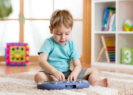 Happy kid boy playing piano toy in nursery