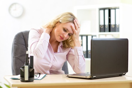 Foto de middle-aged businesswoman with headache having stress in the office - Imagen libre de derechos