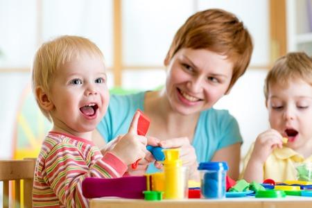 Foto de woman teaches kids handcraft at kindergarten or playschool - Imagen libre de derechos