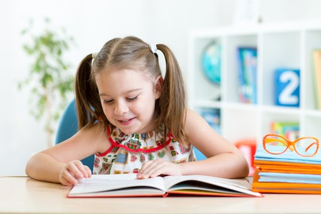 Photo pour Child girl learns to read sitting at table in nursery - image libre de droit