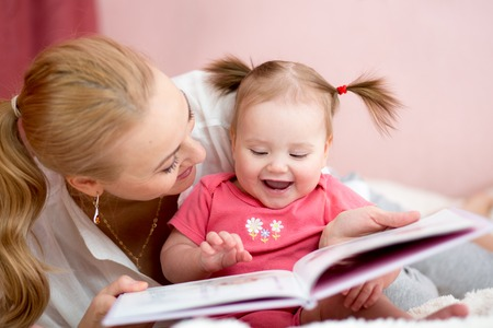 Photo pour happy mother read a book to child girl indoors - image libre de droit