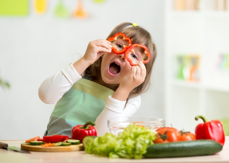 Foto de kid girl having fun with food vegetables at kitchen - Imagen libre de derechos