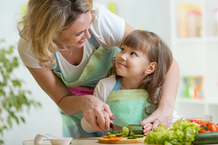 Foto de mother and kid girl cooking and cutting vegetables on kitchen - Imagen libre de derechos