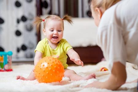 Foto de mom playing ball with baby indoor at home - Imagen libre de derechos