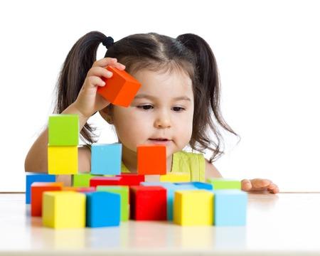 Photo pour toddler kid girl builds a tower with colorful blocks - image libre de droit