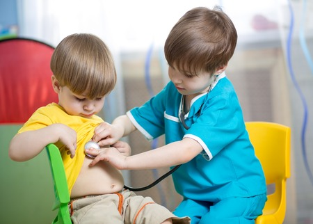 Foto de child boy weared as doctor role playing with his younger brother - Imagen libre de derechos