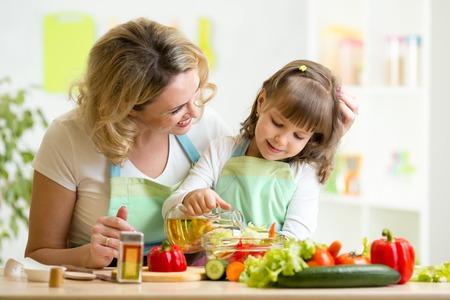 Foto de mom and kid girl preparing healthy food at home - Imagen libre de derechos