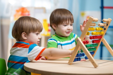 Foto de preschooler children boys play with counter toy - Imagen libre de derechos