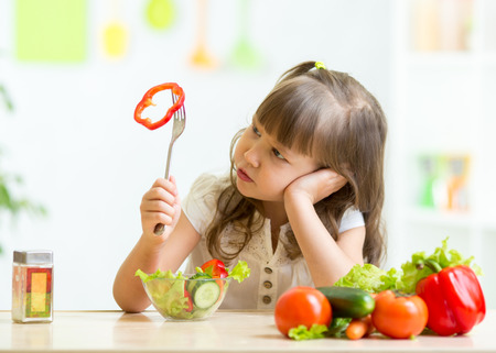 Foto per Cute kid girl not wanting to eat healthy food at kitchen - Immagine Royalty Free
