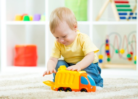 Foto de kid boy toddler playing with toy car indoors - Imagen libre de derechos