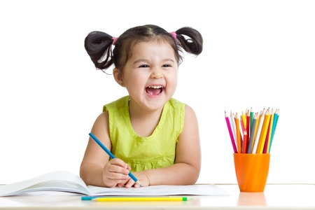 Foto de Adorable child drawing with colorful crayons and smiling, isolated on white - Imagen libre de derechos