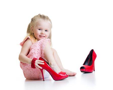 Photo for Little girl trying on mummys shoes isolated - Royalty Free Image