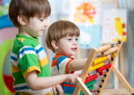 Foto de happy kids brothers play with abacus toy at children room - Imagen libre de derechos