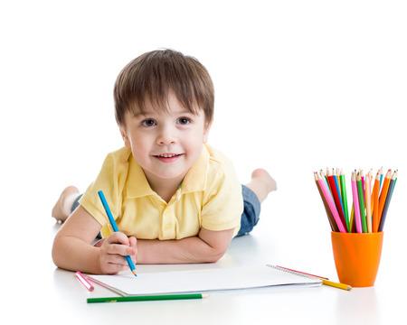 Foto de Cute child little boy drawing with pencils isolated on white - Imagen libre de derechos