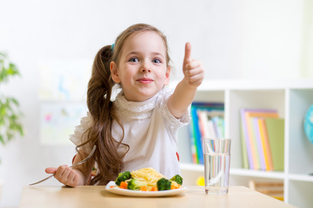 Photo for child girl eats healthy food showing thumb up - Royalty Free Image