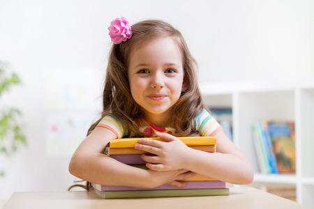 Foto de Cute child girl preschooler with books indoor - Imagen libre de derechos