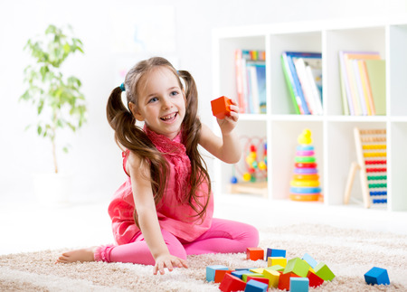 Photo pour kid child girl playing on floor at nursery or kindergarten - image libre de droit