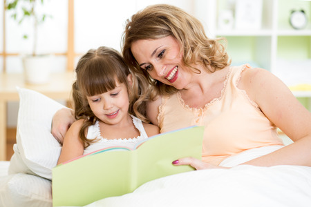 Photo pour Happy mother and daughter read a book together in bed - image libre de droit
