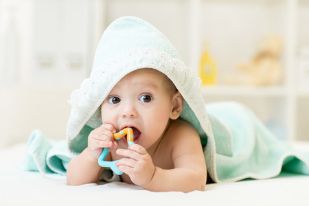 Photo pour baby with teether in mouth under bathing towel at nursery - image libre de droit