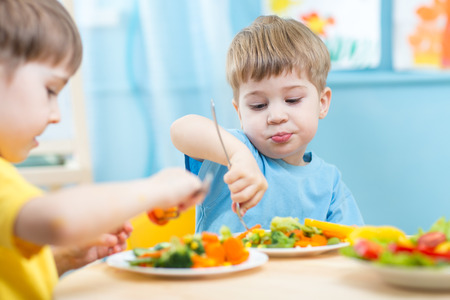 Foto de kids children eating vegetables in kindergarten or at home - Imagen libre de derechos